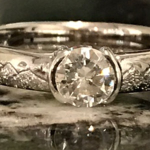 Custom Hand Engraved Engagement Ring features a full round brilliant cut diamond and engraved Alaska mountain scene that encircles the band designed by Giamante Jewelry in Anchorage AK