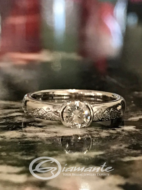 Custom Hand Engraved Engagement Ring features a full round brilliant cut diamond and engraved Alaska mountain scene that encircles the band designed by Giamante Jewelry in Anchorage Alaska